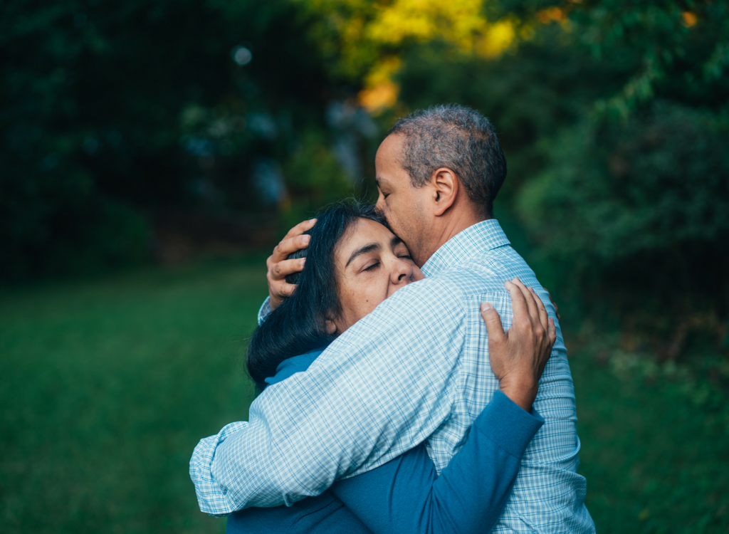 Two adults hugging one another