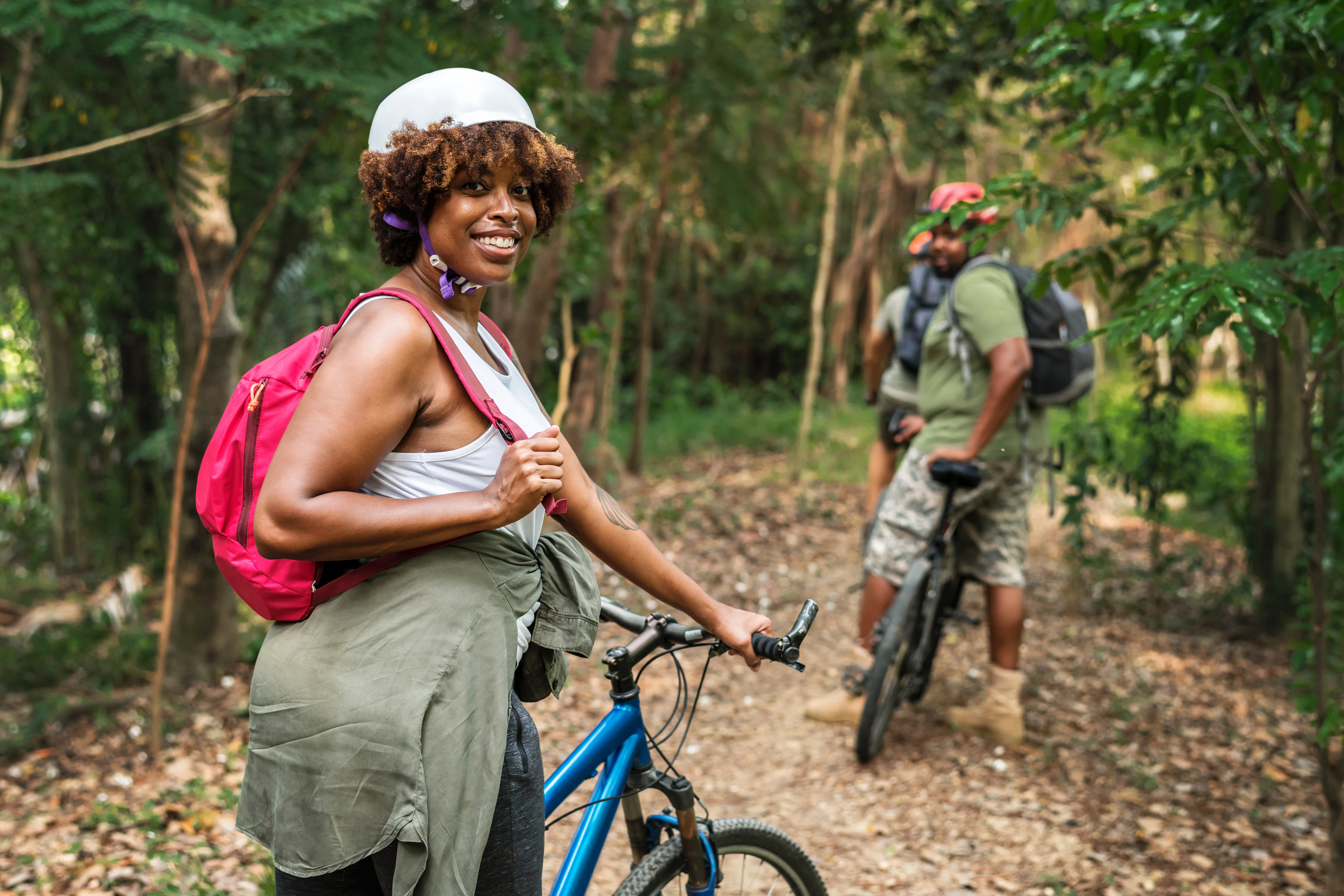 Adult African American female riding bike on trail