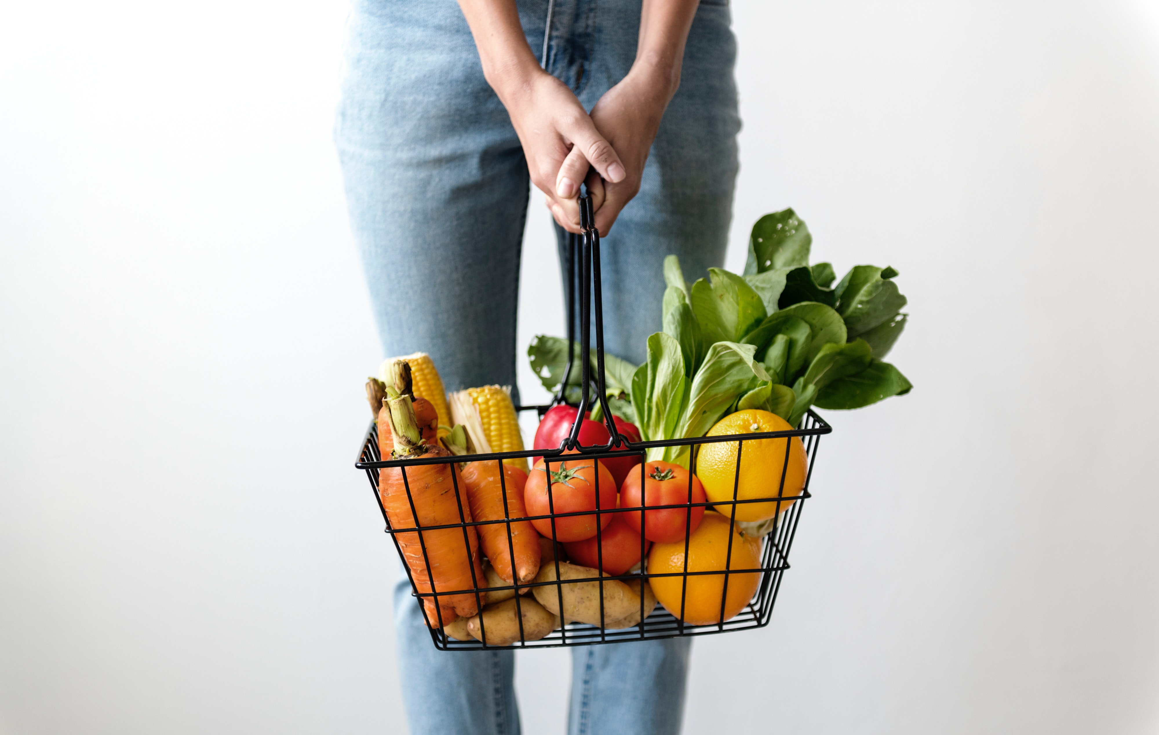 Female holding grocery basket of fruits and vegetables