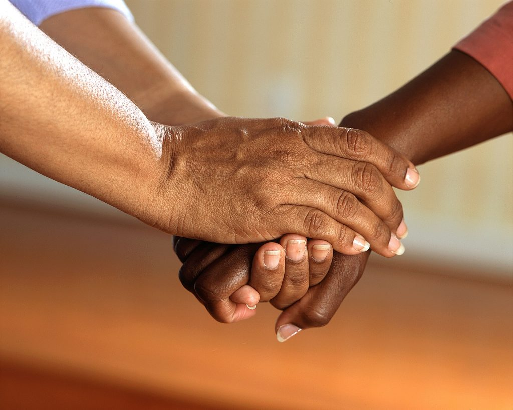 Two individuals holding hands comforting one another