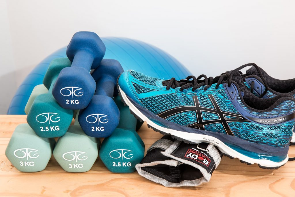 Athletic shoes with dumbbells and exercise equipment