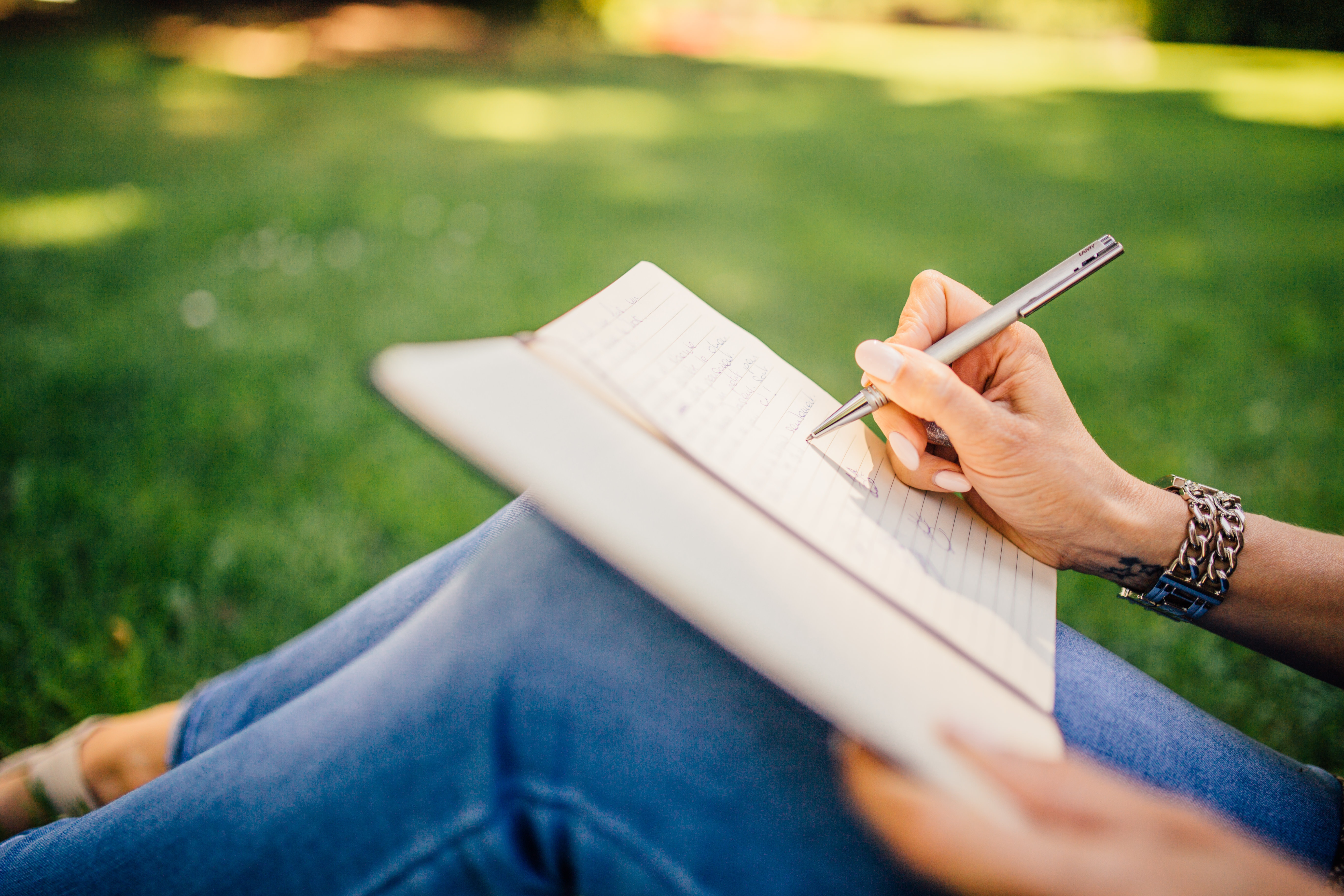 Female writing in journal while sitting in a park