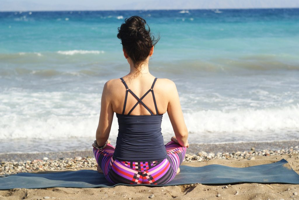 Girl sitting by ocean on yoga mat